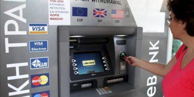 Una mujer sacando dinero de un cajero automático en Nicosia hoy. EFE