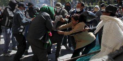 Esposas y policías amotinados se enfrentan a indígenas aimaras fieles al presidente de Bolivia, Evo Morales, en las puertas de palacio de Gobierno en La Paz (Bolivia). EFE