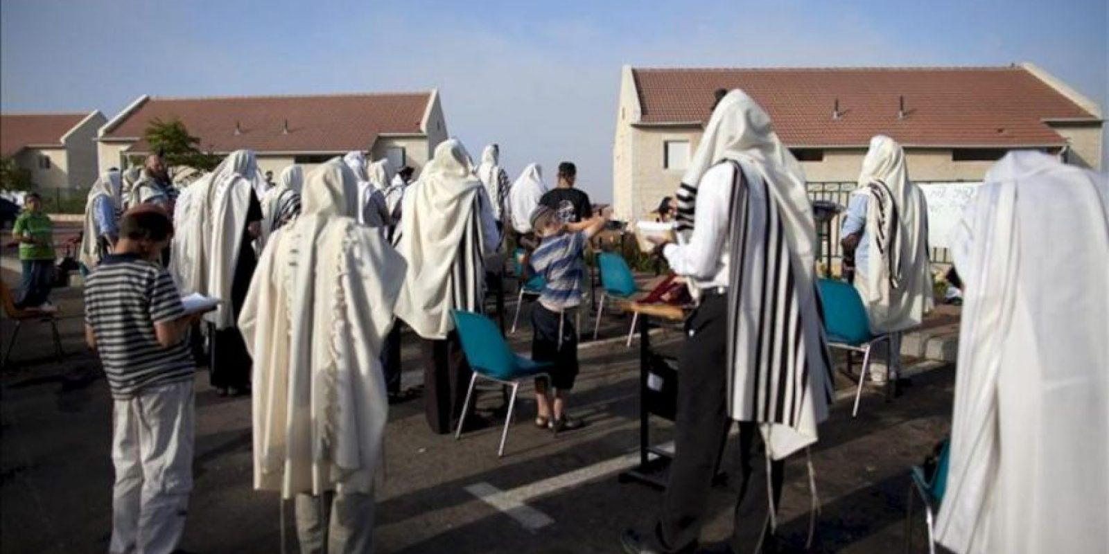 Colonos judíos rezan en un aparcamiento situado frente a las casas que serán demolidas en el barrio de Ulpana, dentro del asentamiento judío de Bet El, en Cisjordania, hoy martes 26 de junio. EFE