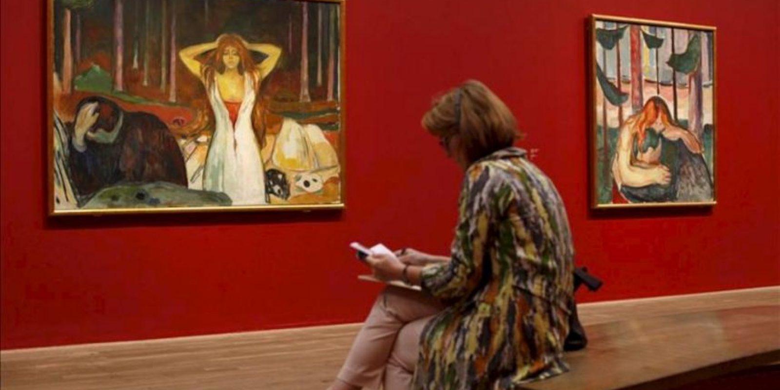 """Un mujer observa los cuadros """"Cenizas"""" (i) y """"Vampiro en el bosque"""", incluidos en la exposición """"Edvard Munch: Modern Eye"""" que se celebra en la Tate Modern de Londres (Reino Unido). EFE"""