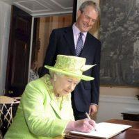 La reina Isabel II de Inglaterra firma en el libro de visitas junto al secretario de Estado de Irlanda del Norte, Owen Paterson, durante la reunión celebrada en el castillo de Hillsborough, en Belfast, Reino Unido, hoy miércoles 27 de junio. EFE