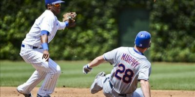 El jugador de los Cachorros de Chicago Starlin Castro (i) trata de coger la pelota mientras el jugador de los New York Mets Daniel Murphy (d) llega a la base durante un partido de las Grandes Ligas, en el estadio de Wrigley Field en Chicago. EFE