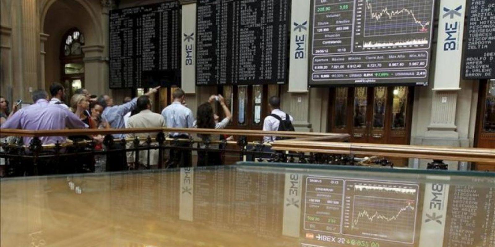 Un grupo de visitantes ante los paneles informativos de la Bolsa de Madrid que muestran distintos índices de cotización entre ellos el principal selectivo español, el IBEX 35, que comenzó la sesión con un fuerte repunte tras los acuerdos alcanzados esta madrugada en Bruselas por los líderes europeos para recapitalizar directamente a los bancos. EFE