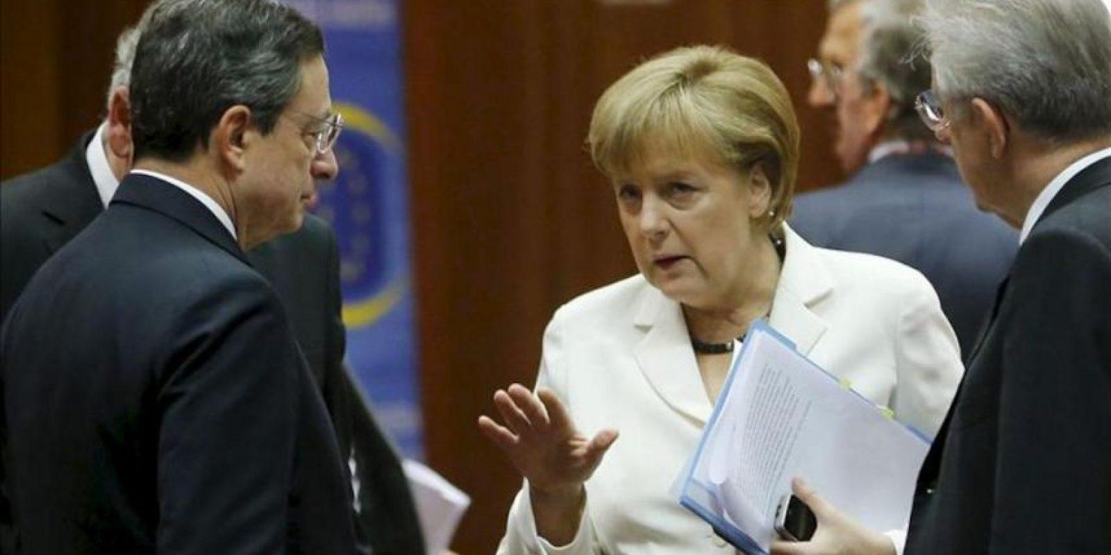 La canciller alemana Angela Merkel (c), charla con el presidente del Banco Central Europeo, Mario Draghi (izq), junto al primer ministro italiano, Mario Monti (der), hoy durante la segunda jornada de la cumbre de jefes de Estado y de Gobierno de la Unión Europea en Bruselas, Bélgica. EFE