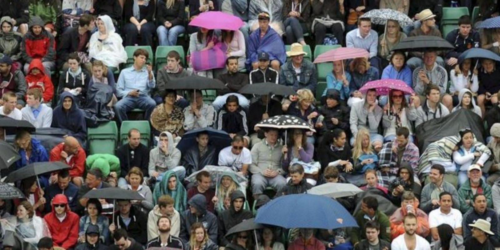Varios aficionados desafían a la lluvia y permanecen en las gradas durante la tercera ronda del torneo de tenis de Wimbledon en el All England Lawn Tennis Club de Londres (Reino Unido). EFE