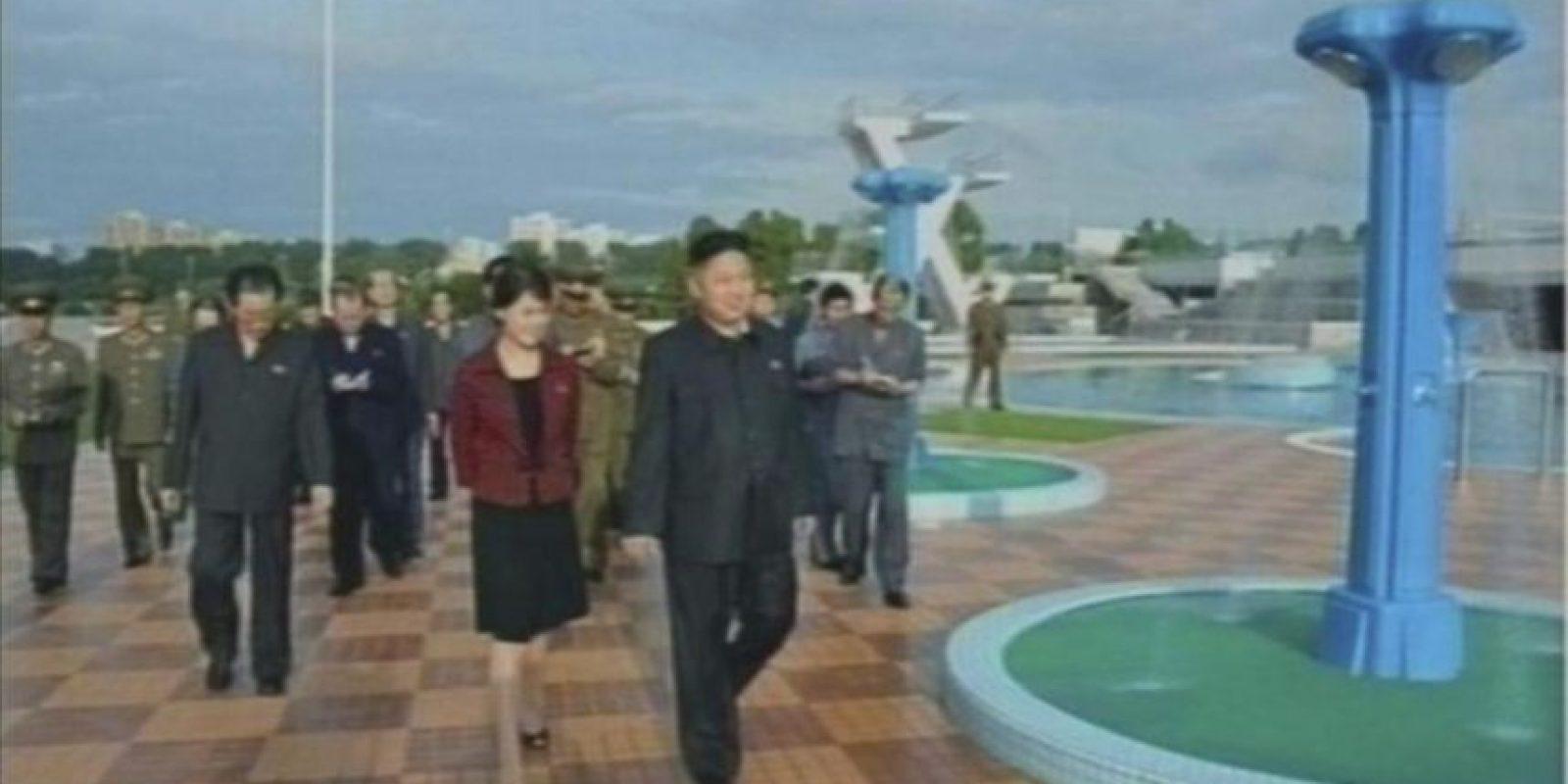 Imagen tomada de un video de la televisión estatal norcoreana hoy, 25 de julio, en la que aparece el líder norcoreano, Kim Jong-un (centro-primer plano), acompañado de la recientemente confirmada como su mujer (a su izq), durante una visita al parque de atracciones Rungra People en Pionyang, Corea del Norte. EFE