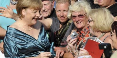La canciller alemana, Angela Merkel (i), saluda a los ciudadanos que esperan la llegada de las celebridades en la apertura del 2012 del Festival de Bayreuth en Bayreuth, Alemania, 25 de julio de 2012. El festival de un mes es el más prestigioso evento de la cultura de Alemania. EFE