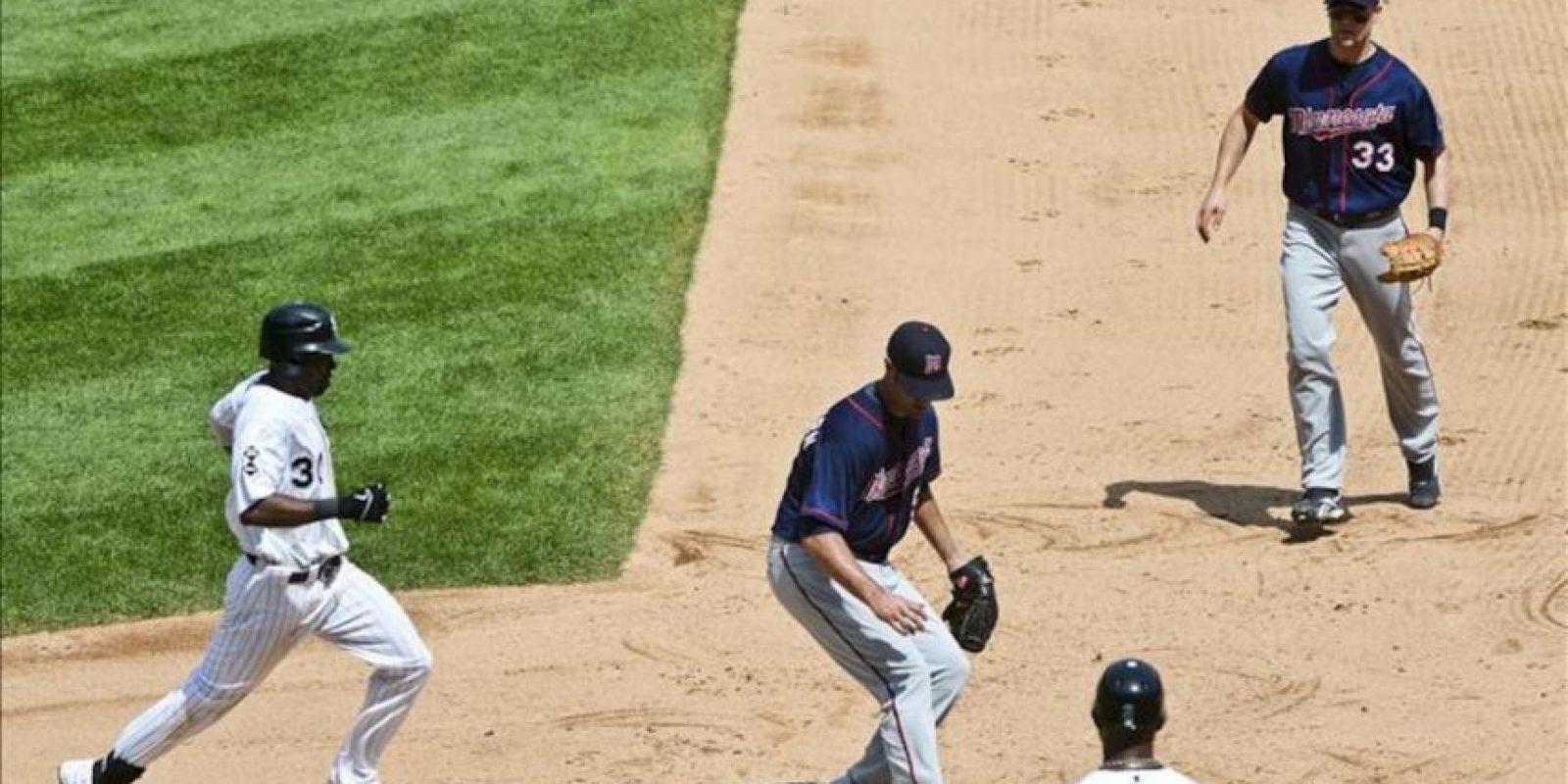 El jugador de los Mellizos, Nick Blackburn (c), en acción ante Alejandro De Aza (i) y Justin Morneau (d) de los Medias Blancas este 25 de julio, durante el juego de la MLB que se disputa en el Cellular Field en Chicago, Illinois (EEUU). EFE