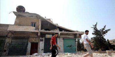 Dos hombres caminan frente a un edificio destruido el 29 de julio de 2012, en una calle de Aleppo (Siria). EFE/Archivo