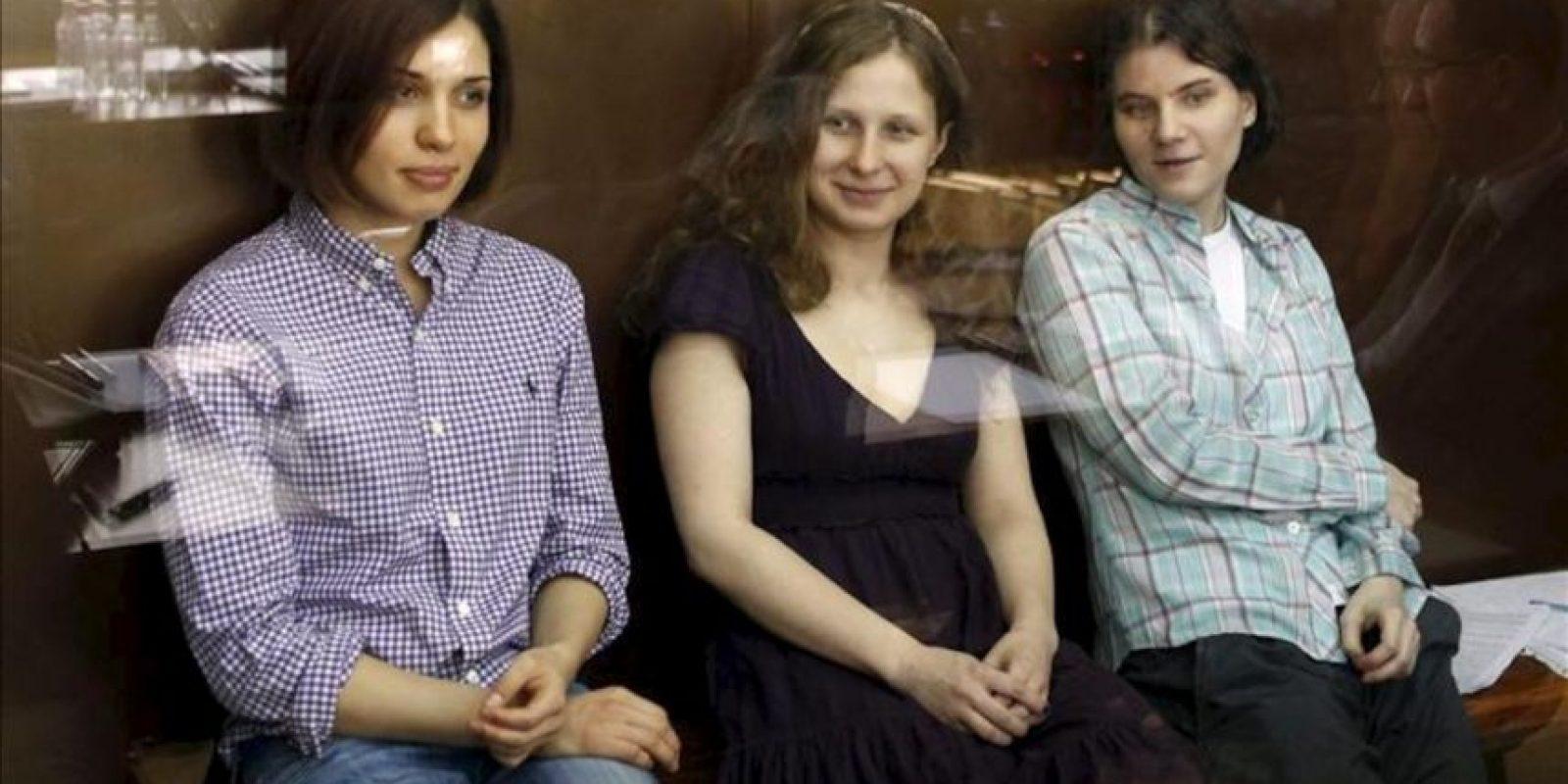 """Las tres integrantes del grupo de punk """"Pussy Riot"""" Nadezhda Tolokonnikova (izq), Yekaterina Samutsevich (der) y Maria Aliokhina (c) se sientan en el banquillo de los acusados en una zona acristalada, a la espera de que comience la sesión de juicio en el juzgado del distrito Khamovnichesky en Moscú, Rusia. EFE"""