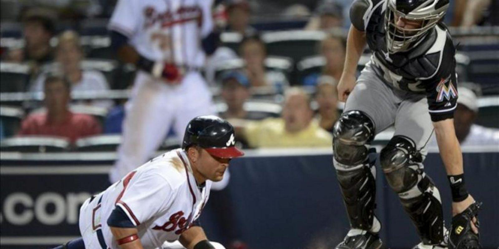 El jugador de Bravos Martin Prado (i) cae para evitar una bola lanzada por Chad Gaudin, de Marlins, durante la quinta entrada de un partido por la MLB en Atlanta, Georgia (EE.UU.). EFE