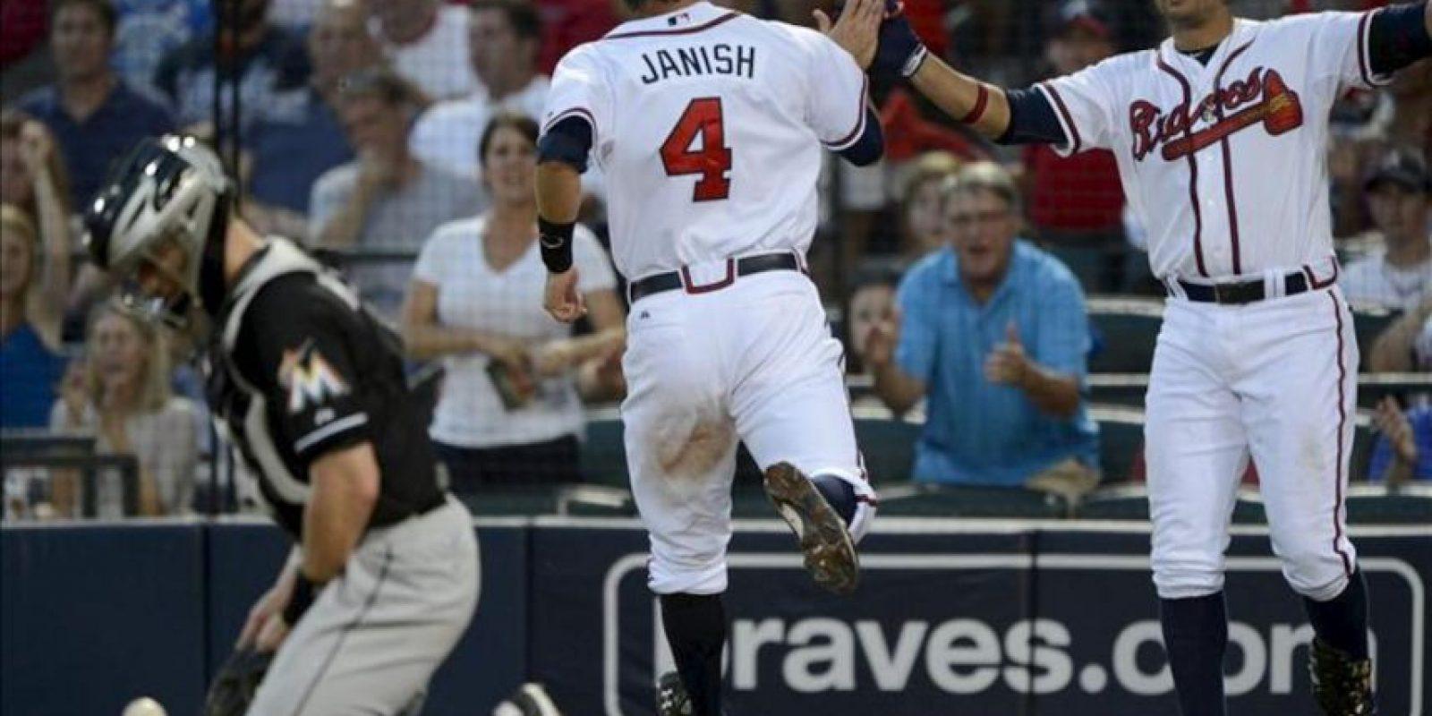 El jugador de Bravos Paul Janish (c) es felicitado por su compañero Martin Prado (d) tras anotar una carrera frente al receptor de Marlins Brett Hayes durante la quinta entrada de un partido por la MLB en Atlanta, Georgia (EE.UU.). EFE