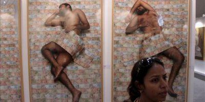 Una mujer pasa delante de una serie de fotos en las que billetes de rupias dan forma a las sábanas entre las que sueña el individuo, una de las obras expuestas en la United Art Fair, la primera feria de arte independiente de Nueva Delhi, en la que cientos de jóvenes artistas de toda la India exponen sus obras. EFE
