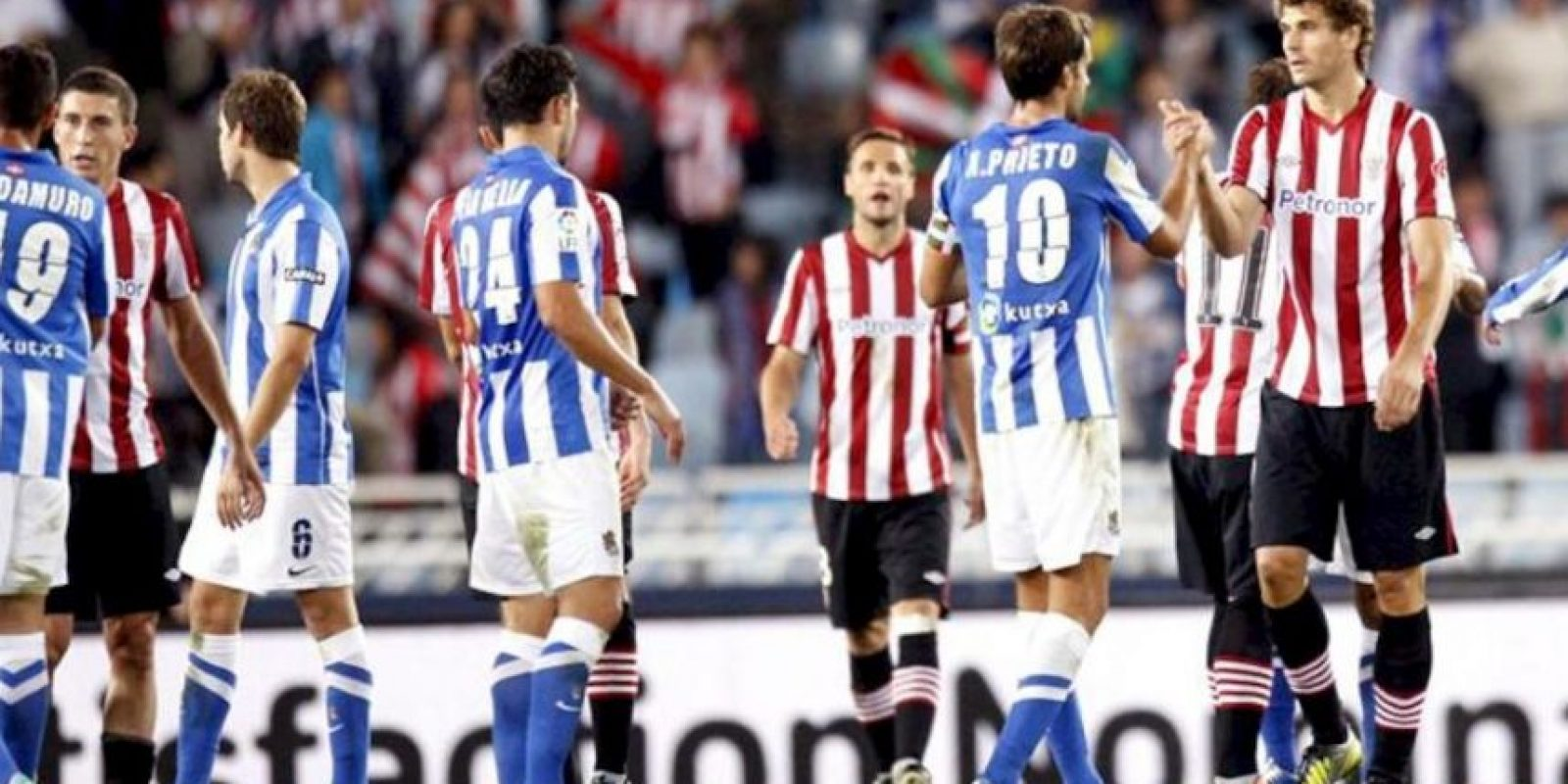 El delantero del Athletic Fernando Llorente (d) saluda al centrocampista de la Real Sociedad Xabi Prieto (2d) tras el partido correspondiente a la sexta jornada de la Liga de Primera División disputado en el estadio de Anoeta de San Sebastián. EFE