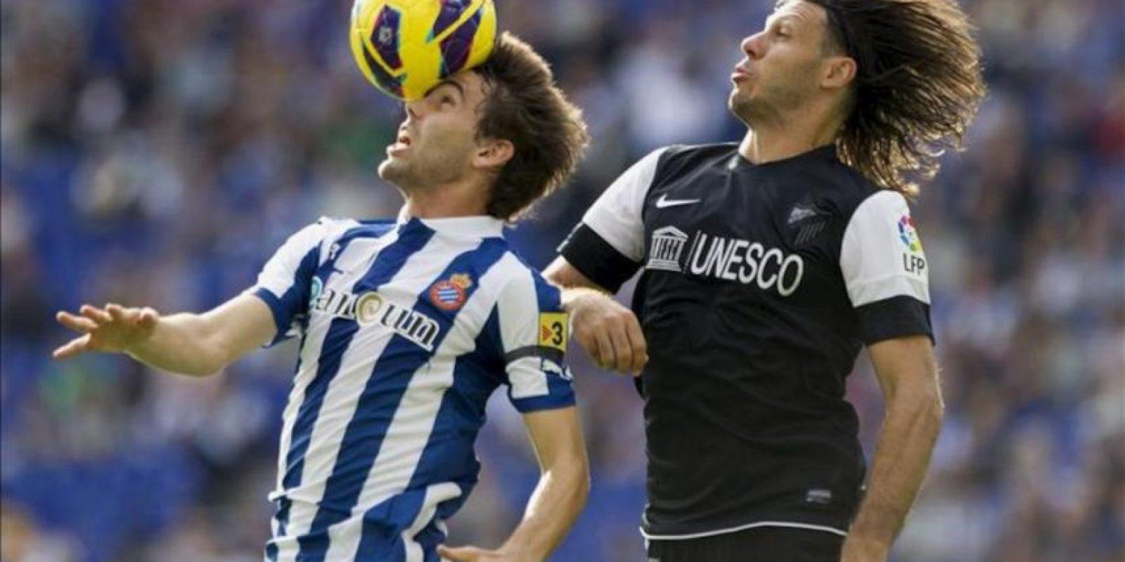 El defensa del Espanyol Víctor Álvarez (i) golpea la pelota presionado por el defensa argentino del Málaga Martín Demichelis, durante el partido correspondiente a la novena jornada de la Liga de Primera División disputado en el estadio Cornellà-El Prat. EFE