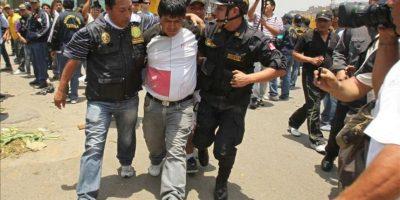 Un manifestante es detenido en las inmediaciones del Mercado de la Parada este 27 de octubre, en Lima, durante los operativos de desalojo del mercado mayorista. EFE