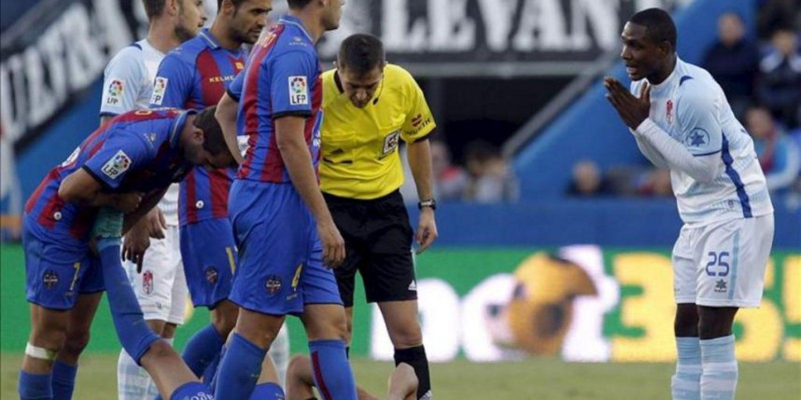 El delantero nigeriano del Granada Odion Ighalo (d) se disculpa tras una entrada sobre un jugador del Levante, durante el partido correspondiente a la novena jornada de la Liga de Primera División disputado en el estadio Ciutat de València. EFE