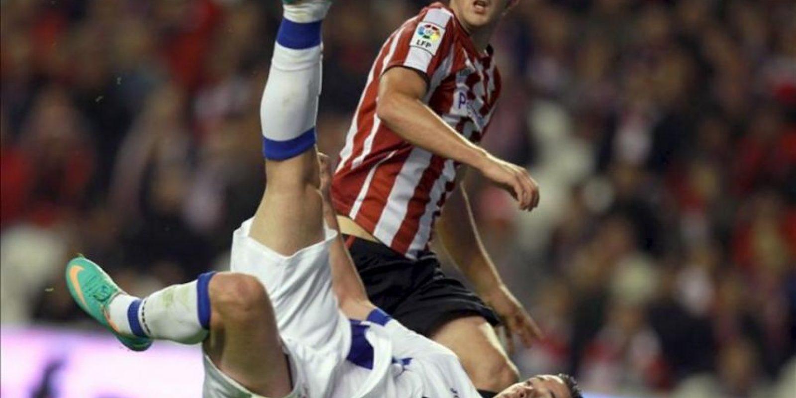 El delantero del Getafe Álvaro Vázquez remata para hacer el segundo gol de su equipo en presencia del defensa del Athletic Mikel San José (detrás), durante el partido correspondiente a la novena jornada de la Liga de Primera División disputado en el estadio de San Mamés de Bilbao. EFE