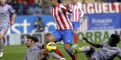 El delantero colombiano del Atlético de Madrid Radamel Falcao (c) intenta marcharse del centrocampista ghanés Anthony Annan (d) y el defensa Alejandro Arribas (i), ambos del Osasuna, durante el partido correspondiente a la novena jornada de la Liga de Primera División disputado en el estadio Vicente Calderón de Madrid. EFE