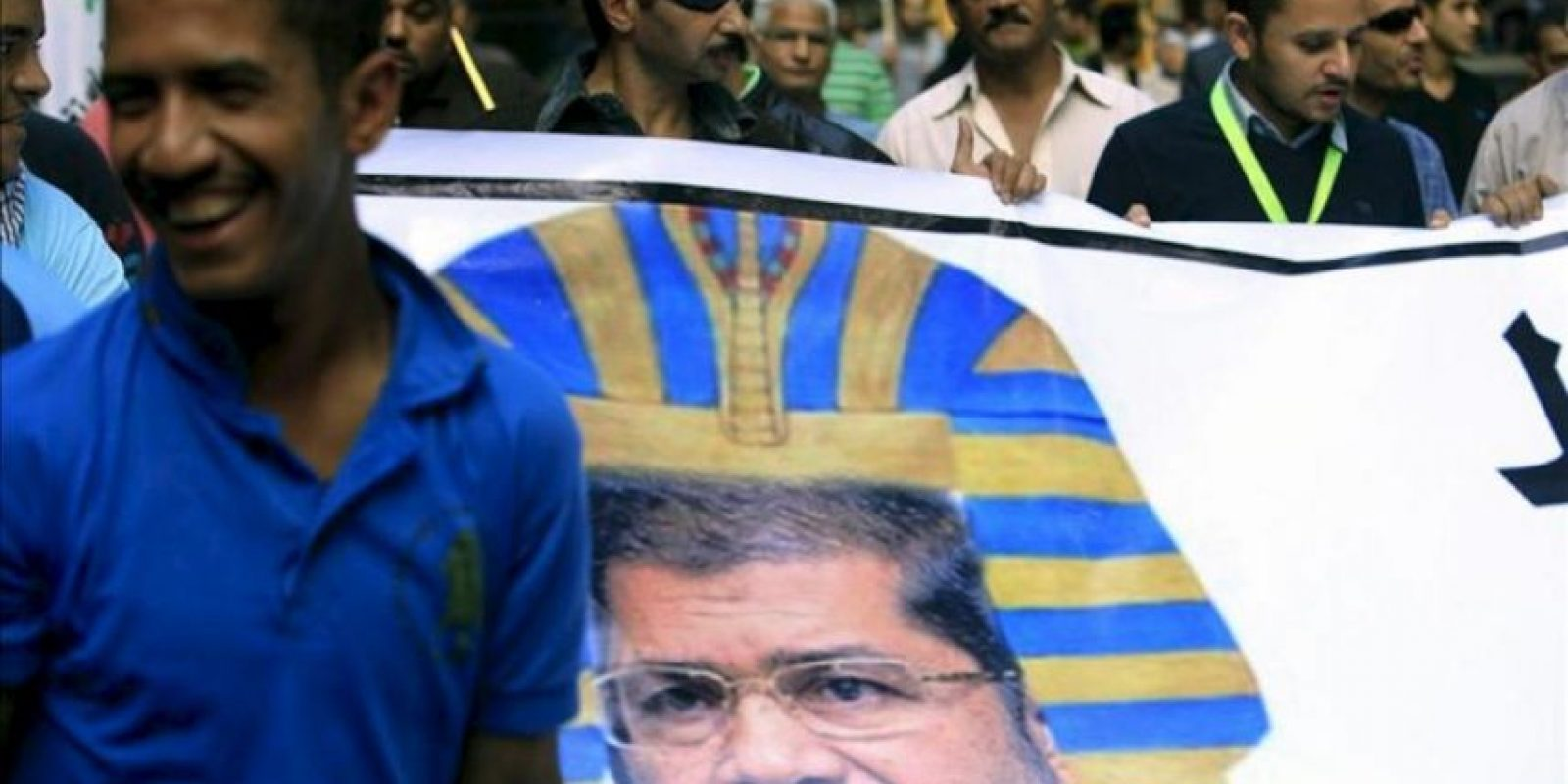 Manifestantes egipcios muestran una pancarta en el que disfrazan al presidente egipcio, Mohamed Mursi, de faraón durante una manifestación organizada por la oposición contra las últimas decisiones del presidente, Mohamed Mursi, que ayer ordenó el blindaje de sus poderes ejecutivos y legislativos ante la Justicia en El Cairo (Egipto). EFE