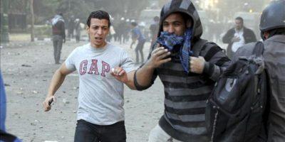 Manifestantes egipcios opositores y simpatizantes del presidente egipcio, Mohamed Mursi, tratan de protegerse de los gases lacrimógenos durante enfrentamientos con agentes de policía antidisturbios en la céntrica plaza Tahrir de El Cairo, Egipto, el 23 de noviembre de 2012. EFE