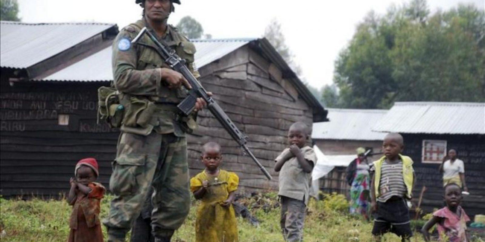 Un soldado de las fuerzas de las Naciones Unidas y un grupo de refugiados desplazados debido a los enfrentamientos entre las fuerzas gubernamentales y los rebeldes M23, desertores del ejercito del DRC, cerca de la capital provincial de Goma, en la República Democrática del Congo. EFE/Archivo