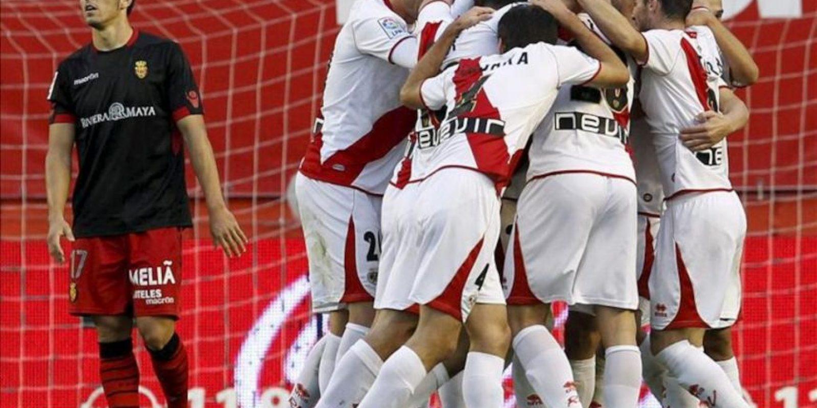 Los jugadores del Rayo Vallecano celebran el primer gol de su equipo, materializado por el delantero brasileño Leo Baptistao, en presencia del defensa del Mallorca, Pedro Bigas (i), en el partido correspondiente a la decimotercera jornada de la Liga de Primera División en el estadio municipal de Vallecas. EFE