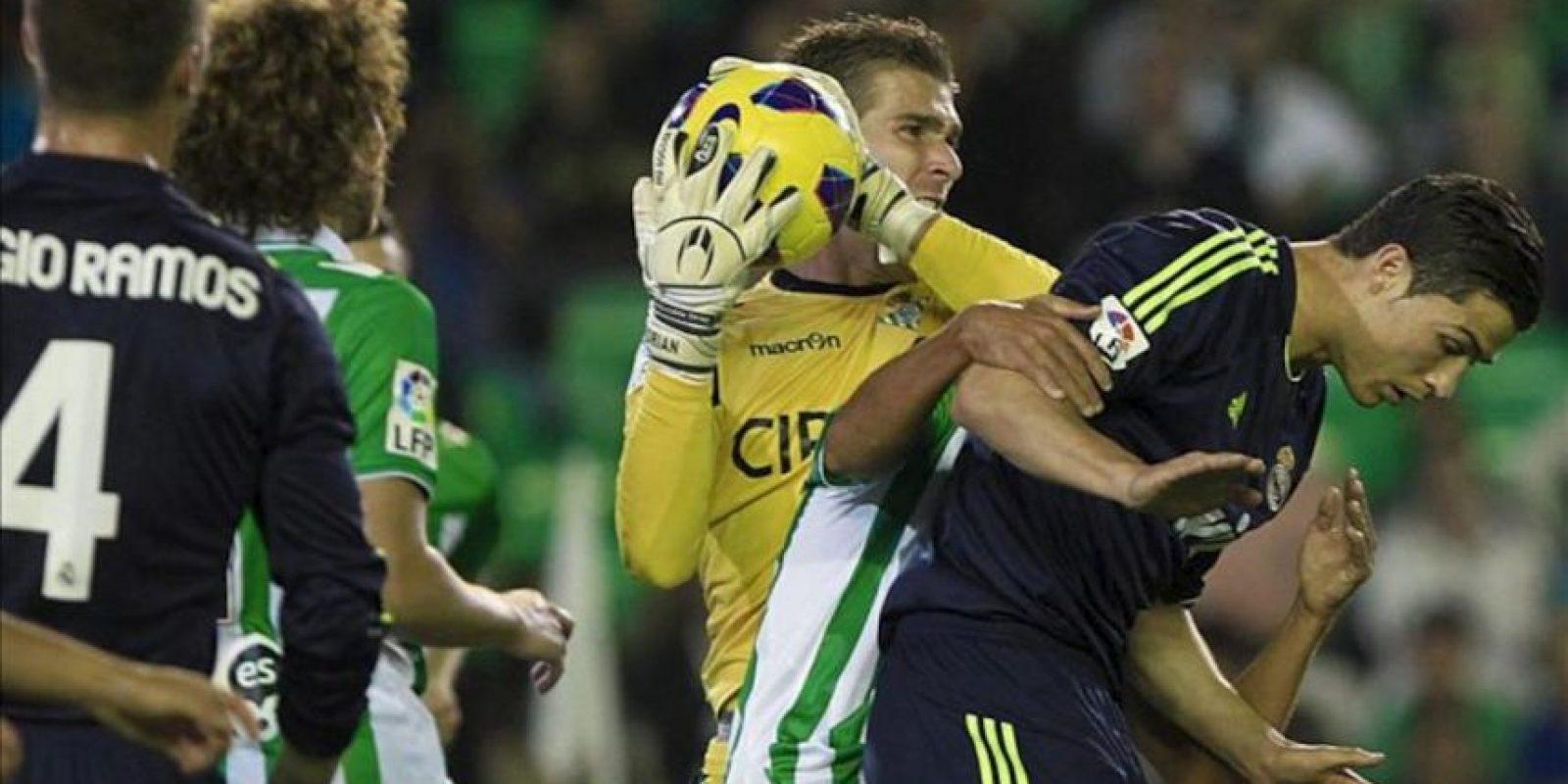 El portero del Betis, Adrián San Miguel (2d), atrapa la pelota en presencia del delantero portugués del Real Madrid, Cristiano Ronaldo (d), en el partido correspondiente a la decimotercera jornada de la Liga de Primera División en el estadio Benito Villamarín. EFE