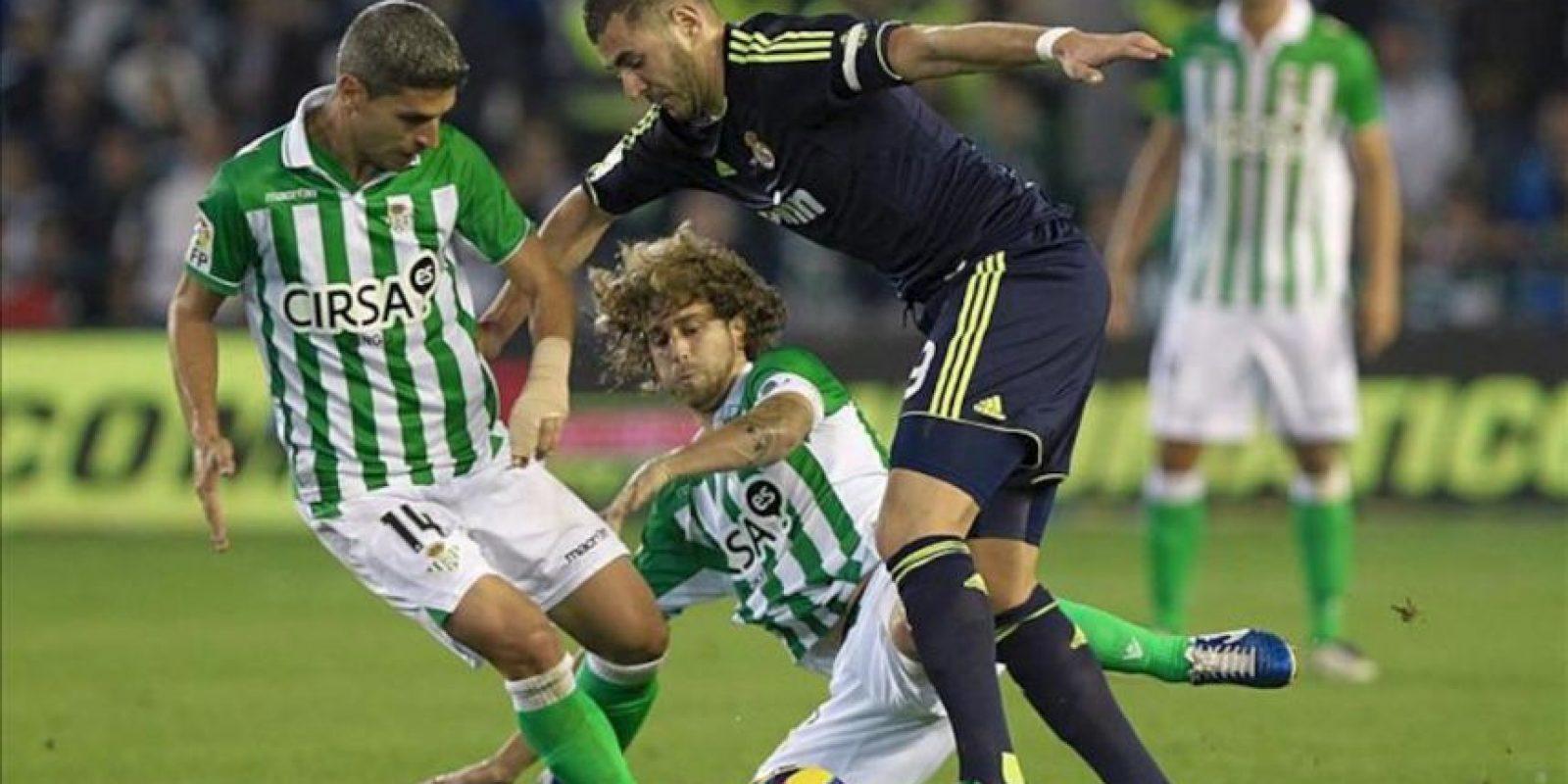 El delantero francés del Real Madrid, Karim Benzema (d) intenta marcharse de los centrocampistas del Betis, Salva Sevilla (i) y José Alberto Cañas (c), en el partido correspondiente a la decimotercera jornada de la Liga de Primera División en el estadio Benito Villamarín. EFE