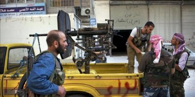Soldados del rebelde Ejército Libre Sirio (ELS) cargando arsenal antiaéreo en una furgoneta aparcada en una calle del barrio de Shaa, en la ciudad siria de Alepo. EFE/Archivo