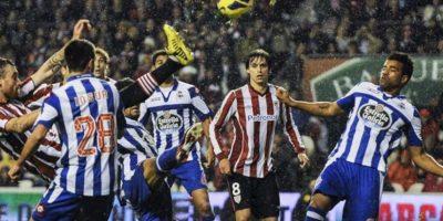 El defensa del Athletic Club Fernando Amorebieta (i) remata el balón ante el delantero del Deportivo de La Coruña Rodolfo Bodipo (d), entre otros jugadores, en el partido correspondiente a la decimotercera jornada de la Liga de Primera División disputado en el estadio de San Mamés. EFE