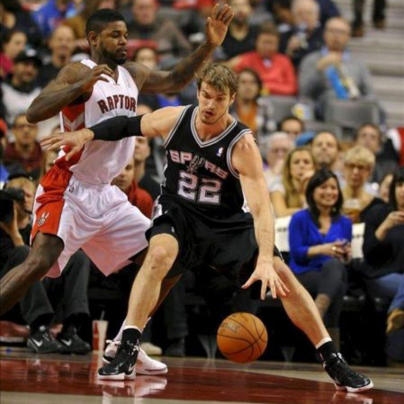 El jugador de los Raptors Amir Johnson (i) bloquea a Tiago Splitter (d) de los Spurs, durante el partido de la NBA disputado en Toronto, Canada. EFE