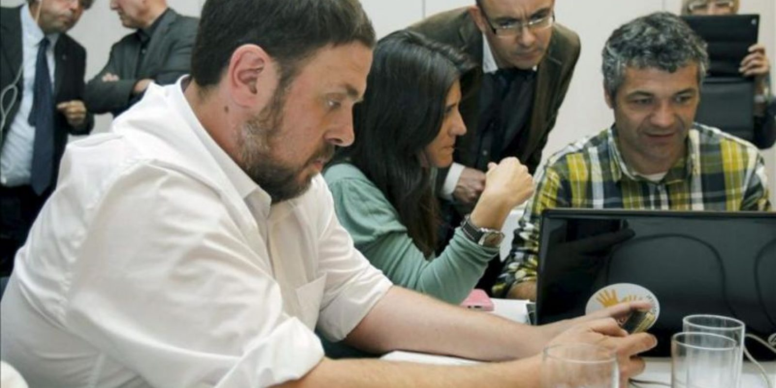 El candidato de ERC (Esquerra Republicana de Catalunya), Oriol Junqueras, sigue el recuento de votos de su partido en las elecciones autonómicas del 25N desde la pantalla de su móvil, al fondo el expresidente del Parlament Ernest Benach (i) y el exconseller de Cultura Joan Manuel Tresserras. EFE