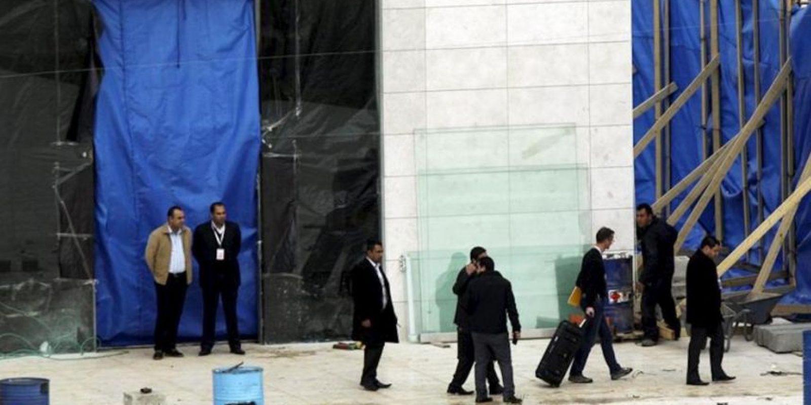 Un hombre (3º dcha), que pudiera ser uno de los investigadores internacionales, carga con una maleta en el mausoleo del que fuera líder palestino Yaser Arafat en Ramala (Cisjordania). EFE