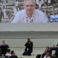 """Participantes atienden al discurso que el fundador de Wikileaks, Julian Assange (en la pantalla), pronunció vía Skype desde la embajada de Ecuador en Londres, donde permanece refugiado desde el pasado mes de junio, durante la conferencia de internet llamada """"Convention Camp"""" en Hanover, Alemania. EFE"""
