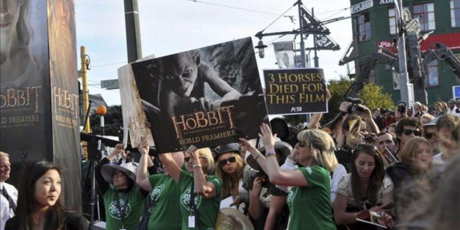 """Miembros de la organización intentan esconder de las cámaras a un grupo de manifestantes defensores de los animales que sostienen una pancarta (dcha) en la que se puede leer """"Tres caballos murieron por esta película"""" en el preestreno de la película """"The Hobbit: An Unexpected Journey"""" (El Hobbit: Un viaje inesperado). EFE"""