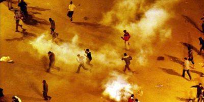 Opositores al presidente egipcio, Mohamed Mursi, corren para evitar los gases lacrimógenos lanzados por policías antidisturbios, durante los enfrentamientos registrados anoche, en las protestas contra Mursi. EFE