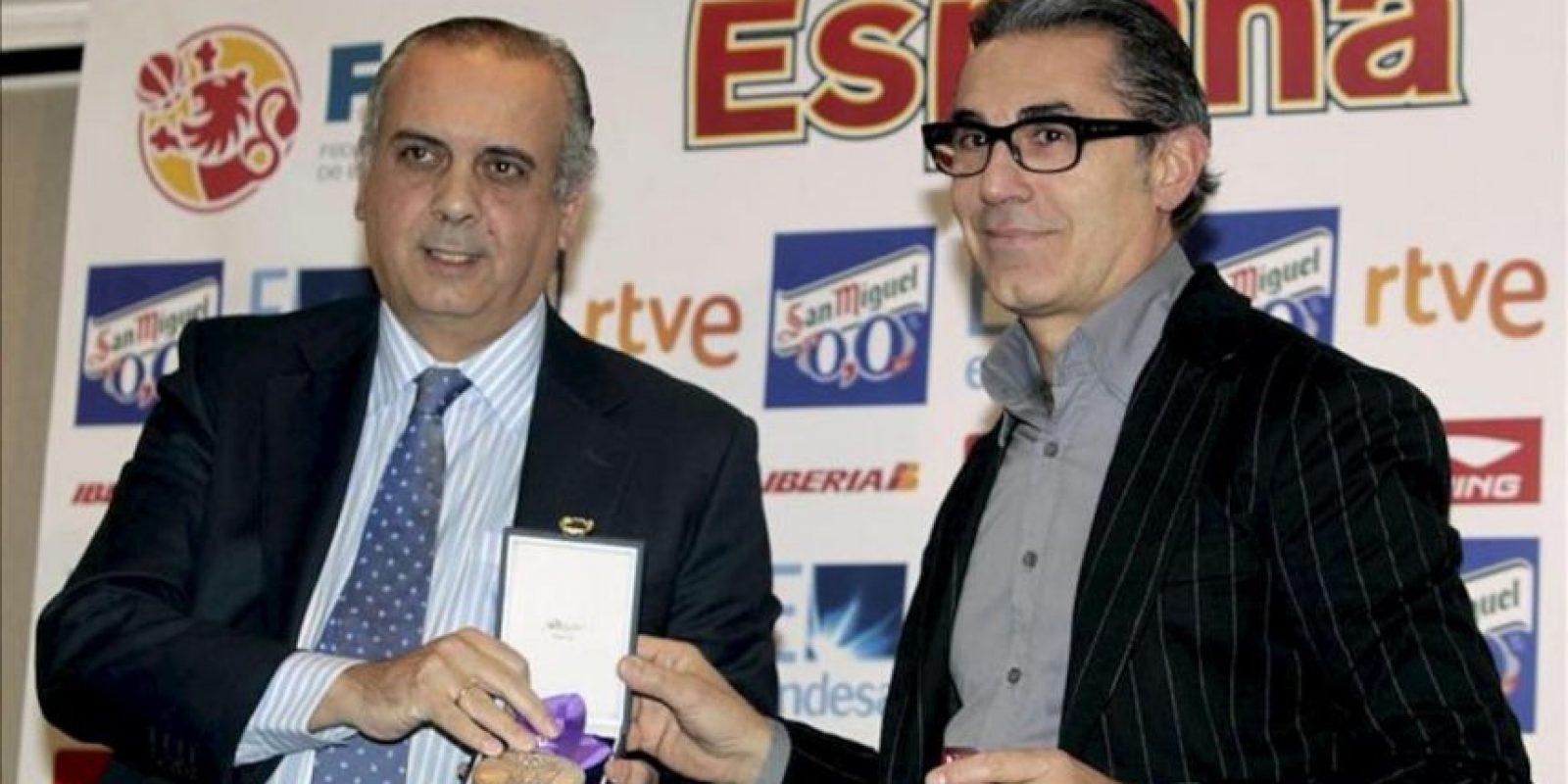 El seleccionador nacional de baloncesto, el italiano Sergio Scariolo (d), recibe de manos del presidente de la Federación Española de Baloncesto (FEB), José Luis Sáez, la medalla de campeón de Europa, durante la rueda de prensa que ha ofrecido hoy en Madrid. EFE