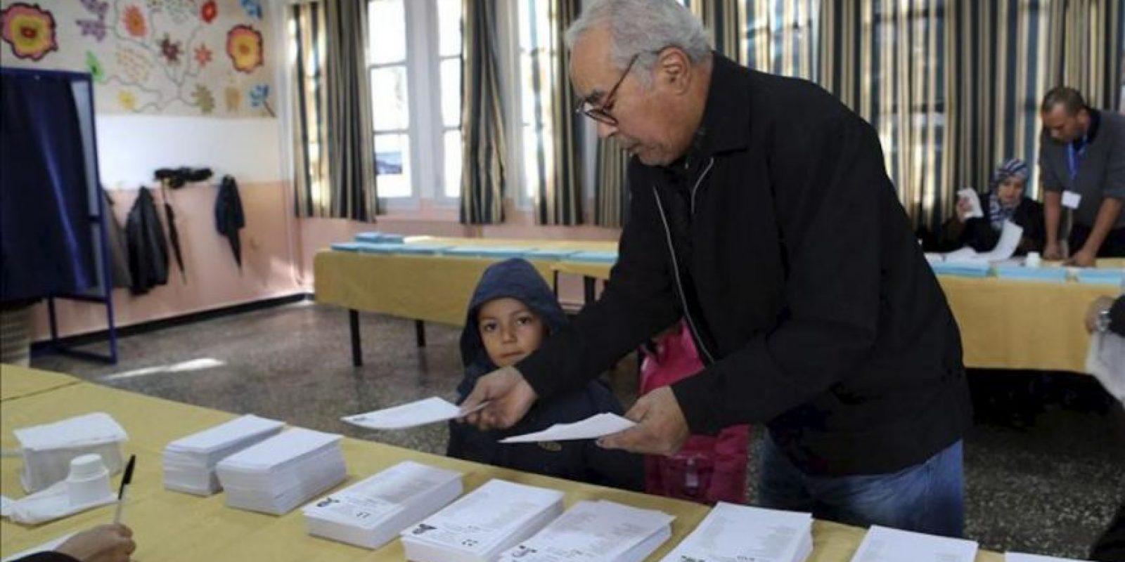 Un hombre escoge una papeleta antes de ejercer el derecho al voto en un centro electoral durante las elecciones locales, en Argel, Argelia. EFE