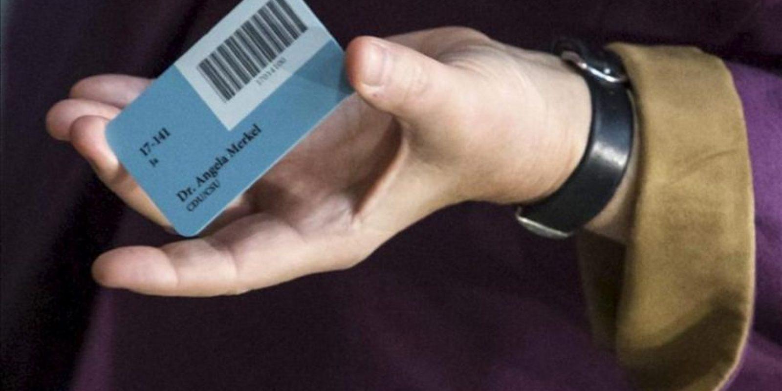 La canciller alemana, Angela Merkel, sujeta su tarjeta de voto parlamentario antes de votar en el Bundestag (Cámara Baja) de Berlín, en Alemania. EFE