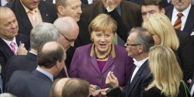 La canciller alemana, Angela Merkel (c), y otros parlamentarios charlan antes de votar hoy en el Bundestag (Cámara Baja) de Berlín, en Alemania. EFE