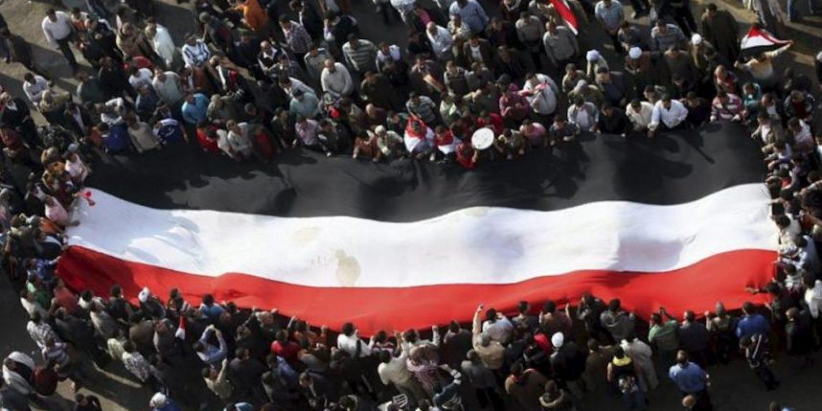 Opositores egipcios despliegan hoy una bandera nacional durante una protesta contra el presidente, Mohamed Mursi, por emitir una declaración constitucional para blindar sus poderes ante la Justicia en El Cairo. EFE