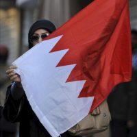 Una mujer que participa en conmemoraciones no autorizadas del Día de los Mártires muestra una bandera bareiní en Manama, Baréin, hoy, lunes 17 de diciembre de 2012. EFE