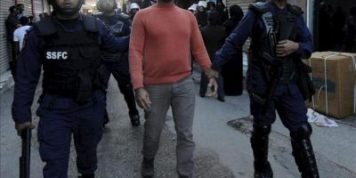 El bloguero Hasan al Yaber (c) es detenido por unos policías antidisturbios que buscan a manifestantes sospechosos de participar en conmemoraciones no autorizadas del Día de los Mártires en Manama, Baréin, hoy, lunes 17 de diciembre de 2012. EFE