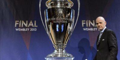 El secretario general de la UEFA, Gianni Infantino, pasa junto al trofeo de la Liga de Campeones tras conocerse el resultado del sorteo de los octavos de final de la Liga de Campeones celebrado en la sede de la UEFA en Nyon, Suiza, hoy, jueves 20 de diciembre de 2012. El Milán y el Manchester United serán los rivales, respectivamente, del Barcelona y el Real Madrid, el Valencia se enfrentará al París Saint Germain francés y el Málaga, debutante en la competición, se medirá al Oporto luso. EFE