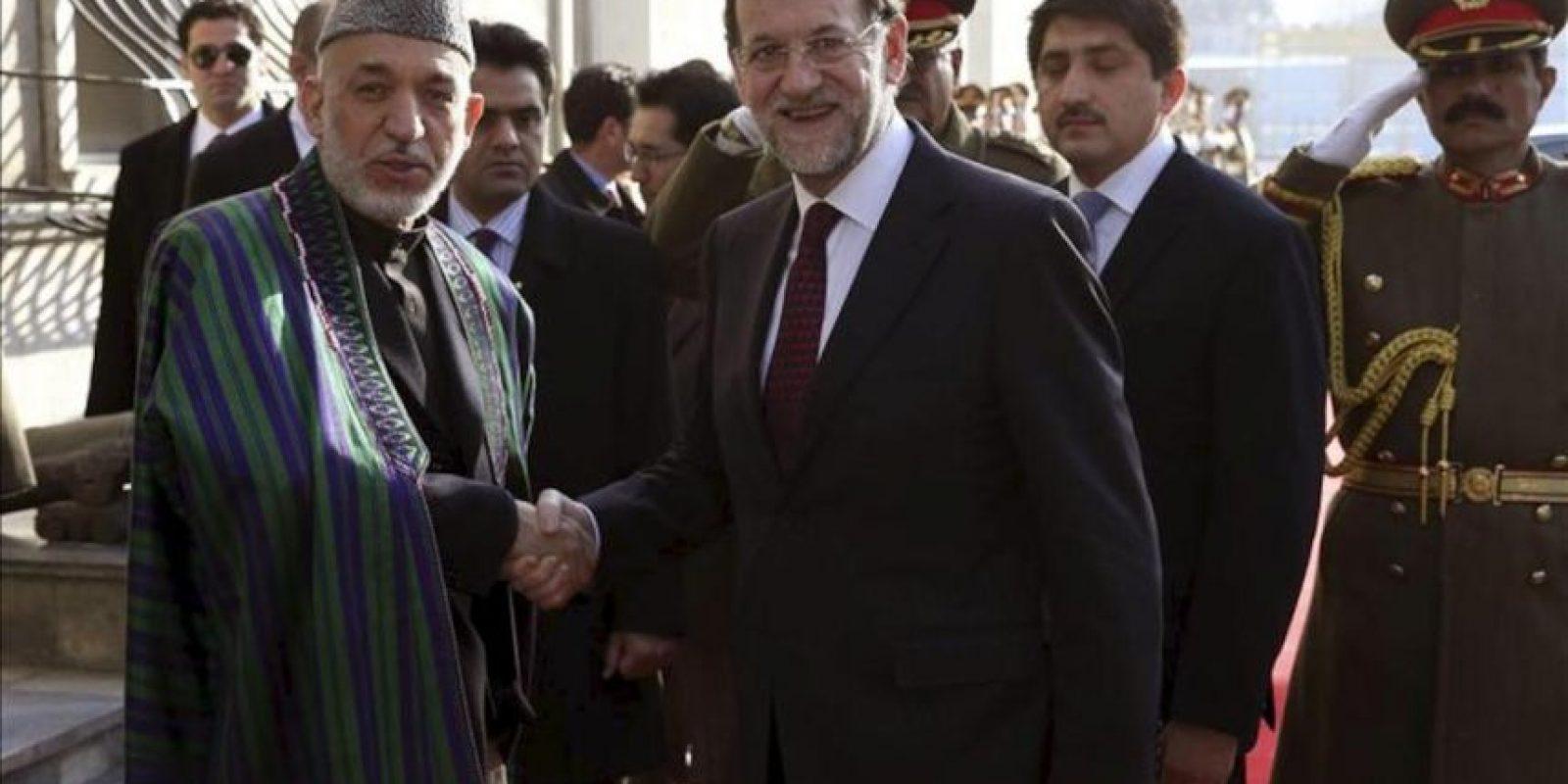 Fotografía facilitada por la Presidencia del Gobierno del jefe del Ejecutivo español, Mariano Rajoy, saludando al presidente afgano, Hamid Karzai, durante su visita por sorpresa hoy a Afaganistan, acompañado por el ministro de Defensa, Pedro Morenés. EFE