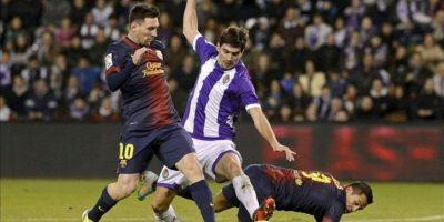 El delantero argentino del F.C. Barcelona Leo Messi (i) pelea un balón con el defensa portugués del Real Valladolid, Henrique Sereno (c) en presencia de su compañero Alexis Sánchez, en partido correspondiente a la decimoséptima jornada de la liga en Primera División disputado en el estadio José Zorrilla de Valladolid. EFE