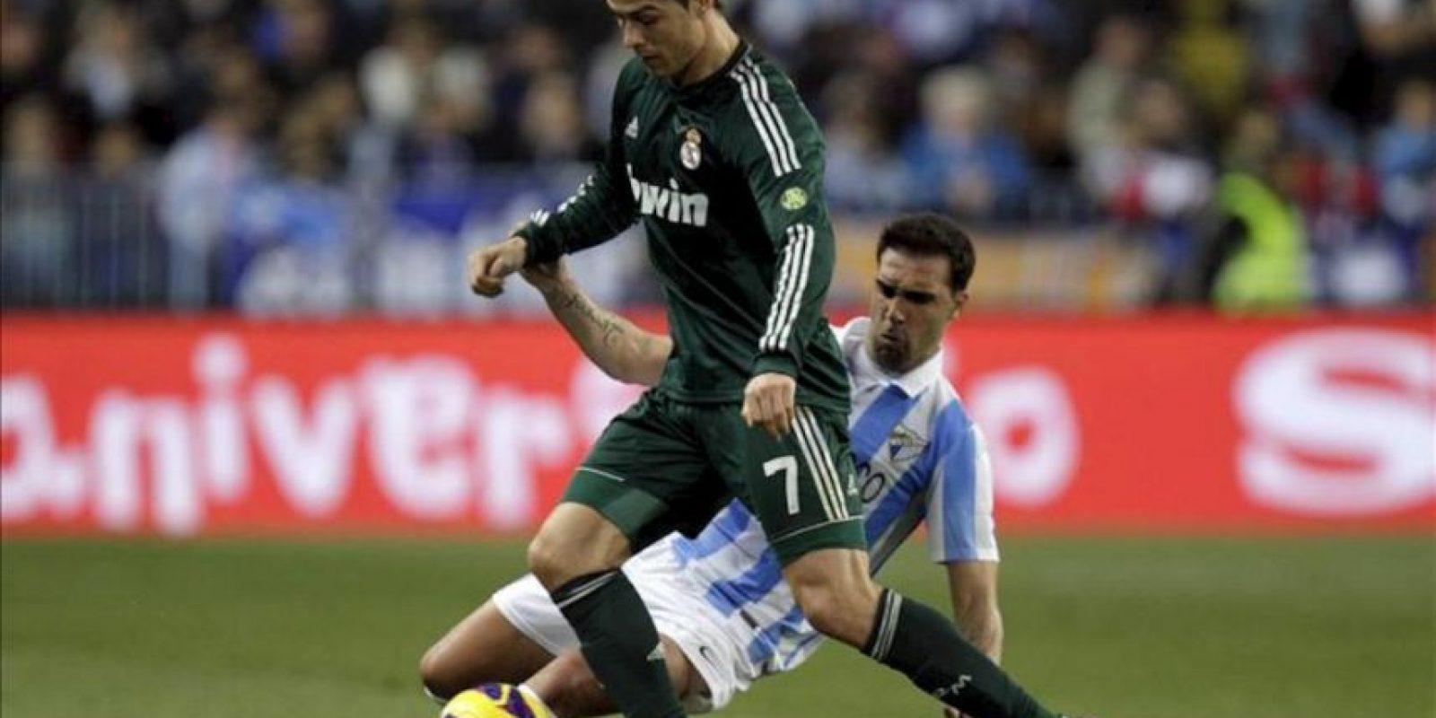 El delantero portugués del Real Madrid Cristiano Ronaldo (i) lucha un balón con Jesús Gámez, del Málaga, durante el partido correspondiente a la decimoséptima jornada de liga en Primera División disputado en el estadio de La Rosaleda. EFE