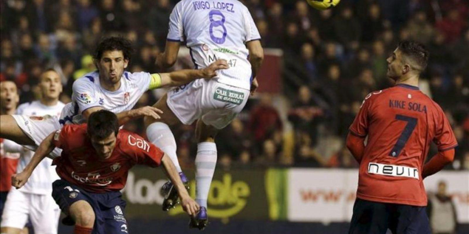 Los jugadores de Osasuna, Llorente (i) y Kike Sola (d), disputan un balón ante los jugadores del Granada, Mainz (i arriba) e Iñigo López, durante el encuentro correspondiente a la decimoséptima jornada de primera división, que han disputado en el Estadio Reyno de Navarra, en Pamplona. EFE