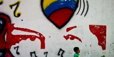 Un niño camina cerca de un grafiti de apoyo al presidente venezolano, Hugo Chávez, en Caracas. EFE